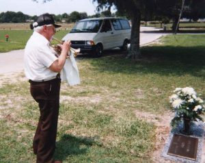 Dad playing hymns at Mom's grave